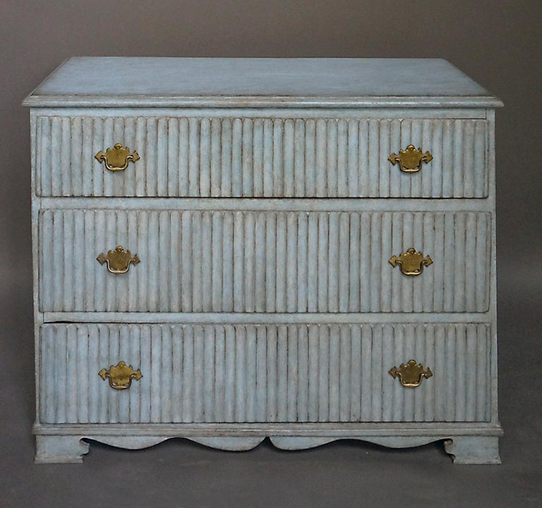 Gustavian chest of drawers, Sweden, circa 1810, with original blue painted surface. The fronts of the dovetailed drawers have strong vertical reeding and original brass hardware. Shaped bracket base.