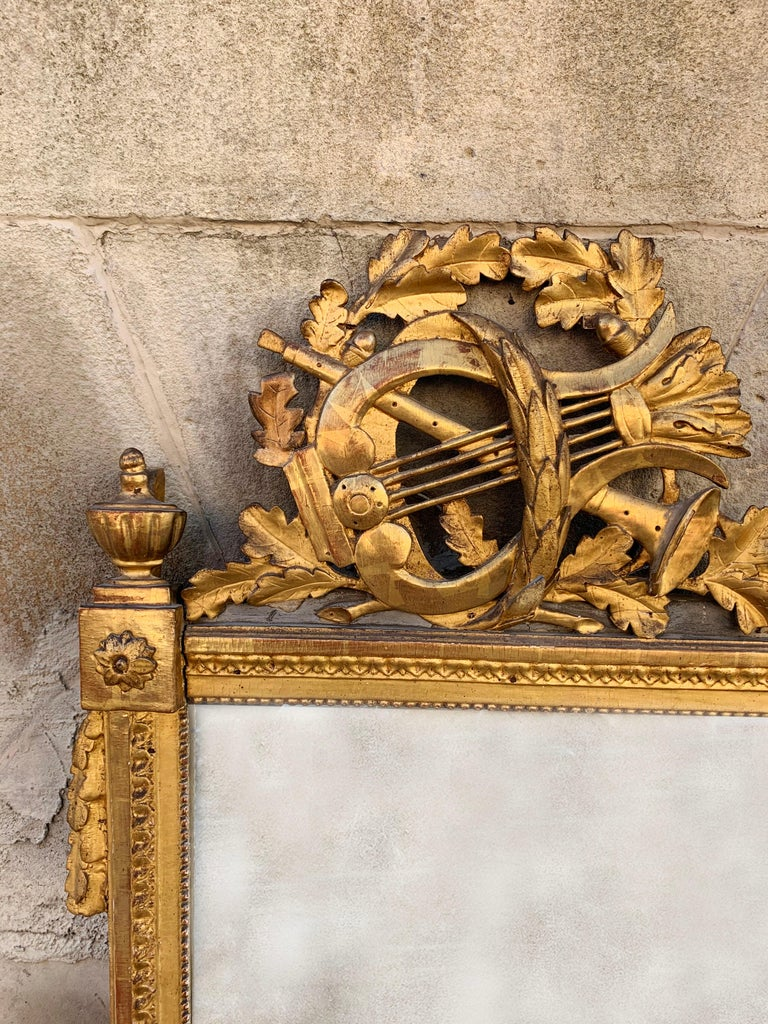 A beautiful gilded looking glass from late 18th century France with beautiful detailing and patina. The corona exhibits a laurel wreath and lyre harp, attributes of the god Apollo. The corners of the mirror frame are decorated with rosettes and the