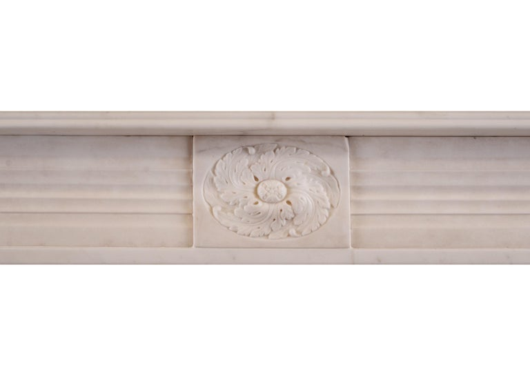 A period English Regency fireplace in statuary marble. The jambs with half rounded reeds surmounted by roundel end blockings. Carved central paterae to frieze, English, circa 1820. One of a very near pair with stock no 3960.