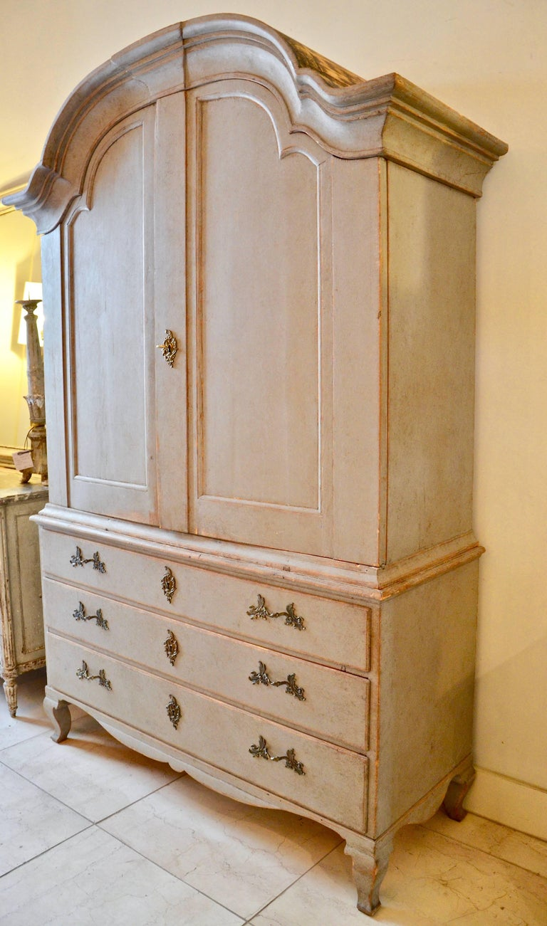 18th century period Swedish rococo cabinet in two parts with bonnet top, raised panel doors, three shelves, four small drawers and a notched spoon shelf, supported by sturdy three drawer base with a scalloped apron and cabriole legs.