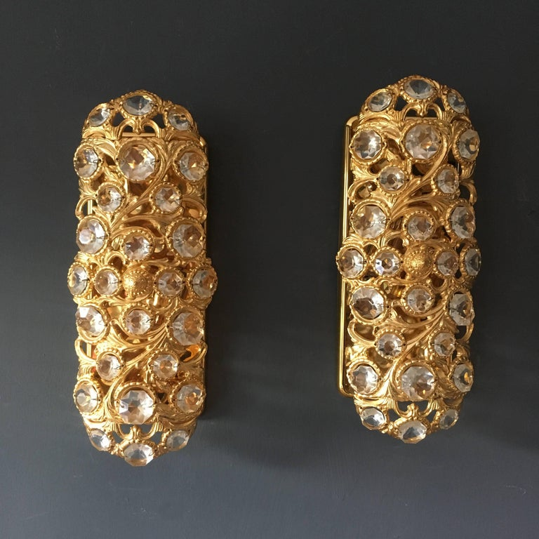 A pair of Peris Andreu gold toned crystal wall lights for S A Riper  Valencia, Spain, circa 1960s.  The lights are in a heavy gold toned metal with reverse prism glass crystals. The gold metalwork is crafted in a Baroque style pattern of