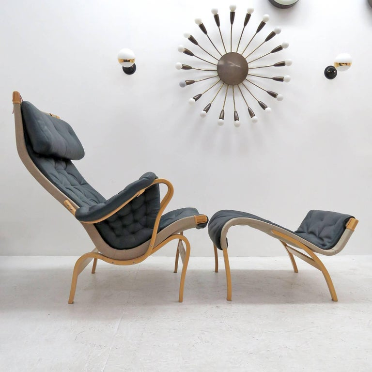 Wonderful early curvilinear lounge chair and ottoman by Bruno Mathsson for DUX, composed of a tufted dark forest green leather cover on canvas, supported by a molded beech plywood frame, with adjustable leather headrest on leather straps, stamped,