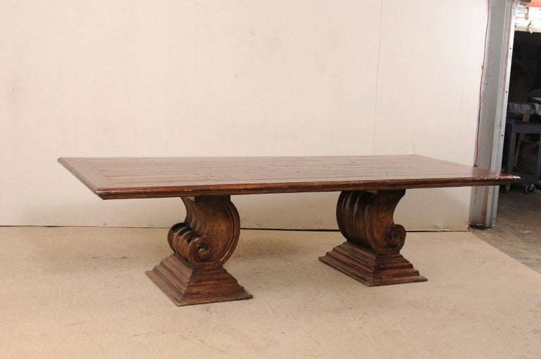 A vintage Brazilian dining room or conference table made of reclaimed peroba wood. This 9.5 foot long table from Brazil features a rectangular-shaped top, raised upon a pair of fabulous volute scrolled pedestal bases. Each of the bases (or legs) are