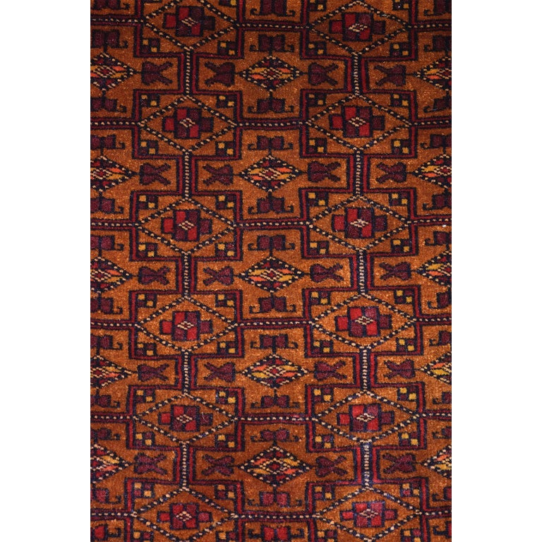 This Persian Balouchi carpet in handspun wool and vegetable dyes circa 1930 exhibits an all-over geometric design in rich golds and reds, with touches of blue and yellow throughout the field and borders. Intricate and sophisticated in its execution,