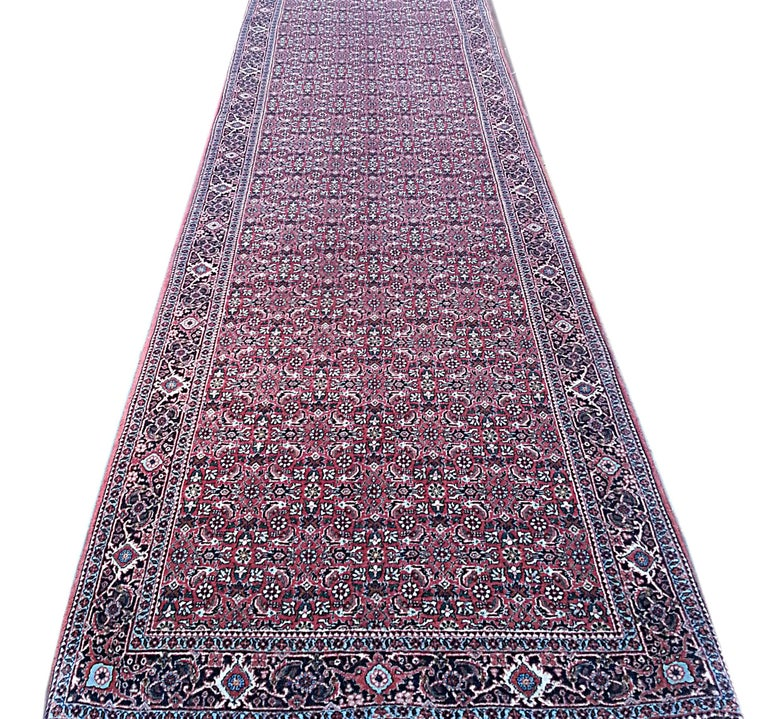 This Authentic beautiful oversized Bijar runner has wool pile and cotton foundation. The rug is all-over floral which is called Herati design. The color combination in this piece is red, cream and blue. Bijar rugs are well known for their