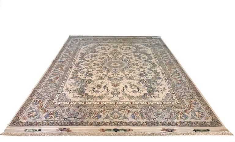 This rug is a hand knotted master piece Persian Tabriz rug with a great quality. This rug features a floral medallion pattern and has designed by Nouvinfar which you can see the signature of the weaver in this beautiful piece. The pile is wool and
