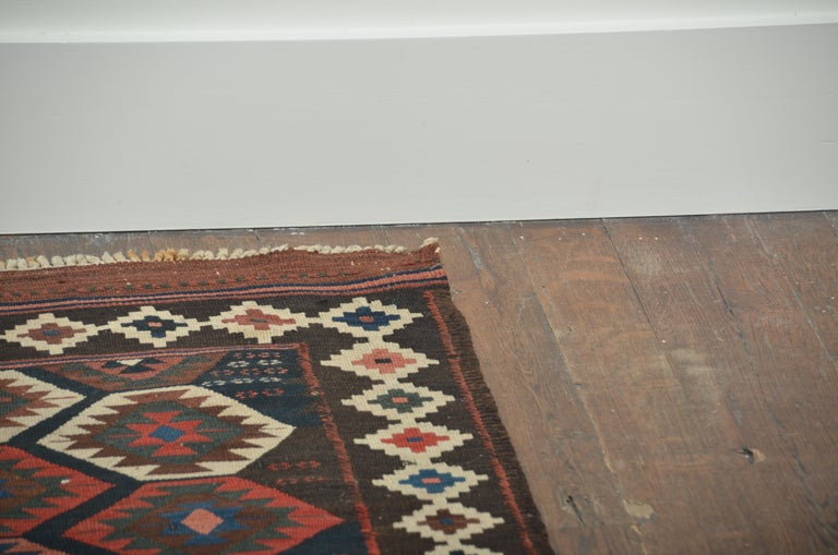 Strong flat-woven rug containing diagonal medallions in rich vegetable dye colors of black, brown, ivory and terracotta. Complementary border of star design.