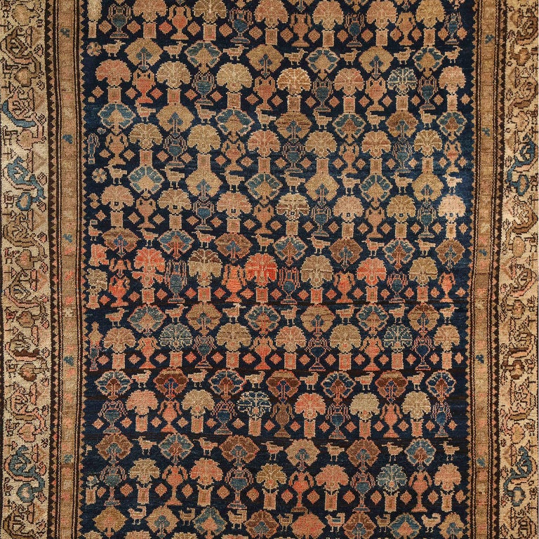 This Persian Malayer carpet circa 1900 consists of pure handspun wool and vegetable dyes. It is hand-knotted on a cotton warp and wool weft, featuring natural hues of indigo, gold, light blue, and orange amid neutral creams and tans. The colors have