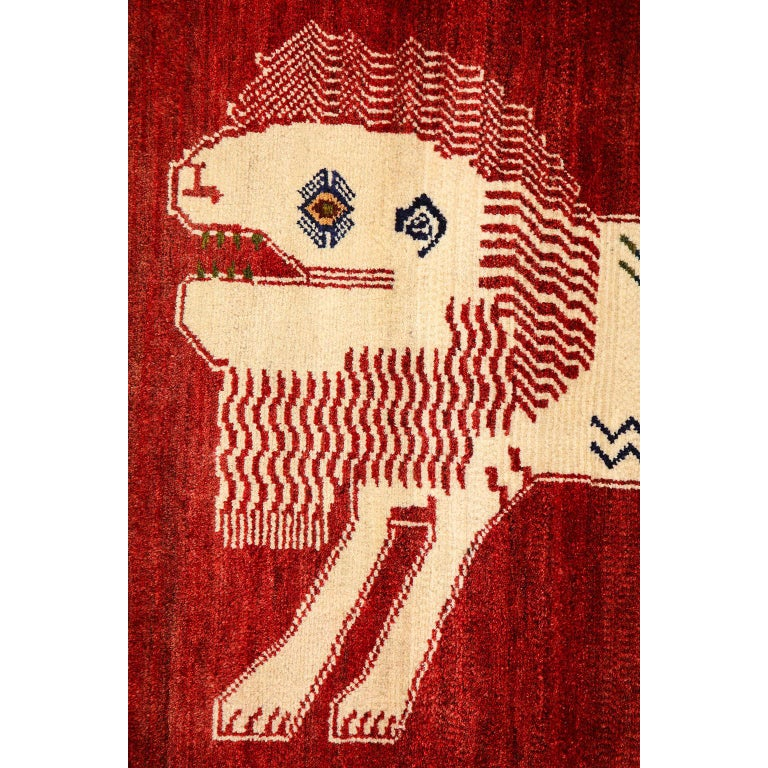 This Persian Qashqai Kashkooli lion animal carpet in handspun wool and vegetable dyes consists of a handspun wool warp, weft and pile. The contrasting color palette of rich red and natural beige creates a bold effect, emphasizing the powerful