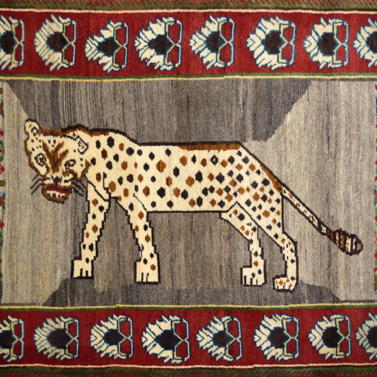 """Hand-knotted in red, cream, grey, brown, green, blue, and gold handspun wool, this Persian Qashqai carpet measures 3'8"""" x 5'11"""" and have a distinctive prowling leopard design. Plush, functional, and resilient in quality, the hand-knotted weave"""