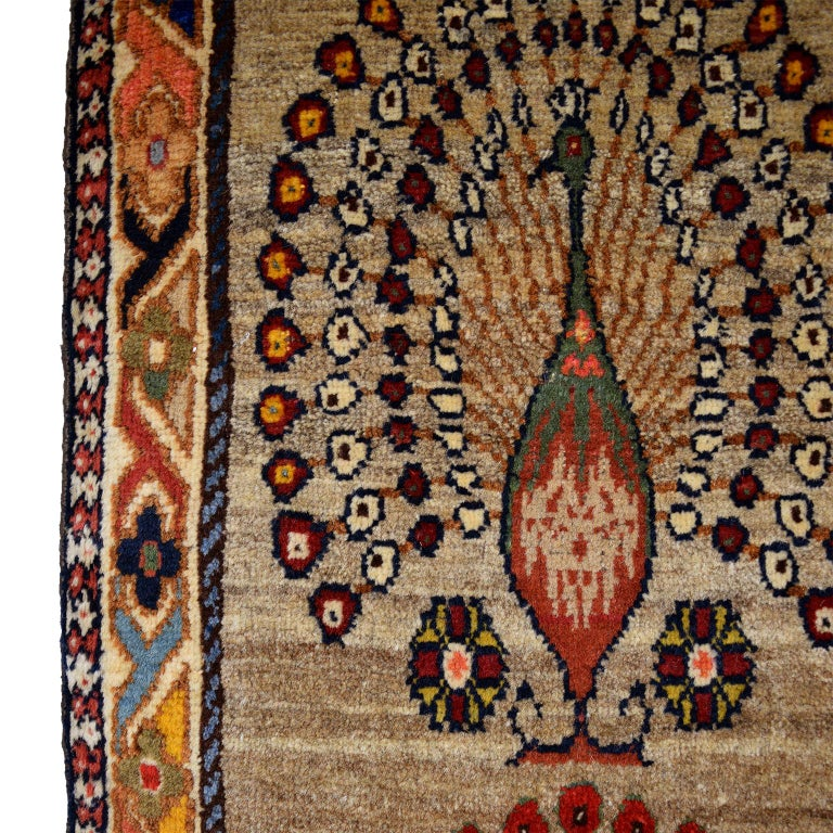 This Persian Qashqai peacock carpet in pure handspun wool and vegetable dyes circa 1940 originates from the Yalameh region and displays four alternating rows of three peacocks each. The bright coloration of the peacocks in blues, greens, coppers,