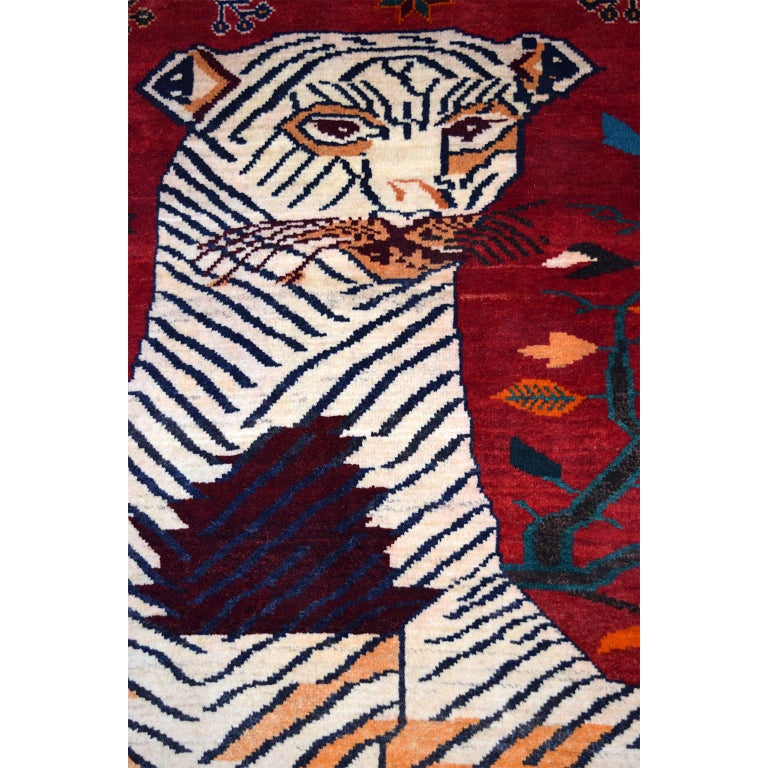 This Persian Qashqai Tiger carpet in pure handspun wool and vegetable dyes circa 1940 exhibits a colorful tiger design in reds, oranges, golds, blues, and cream. The figure of the tiger dominates the field, balanced by geometric floral motifs