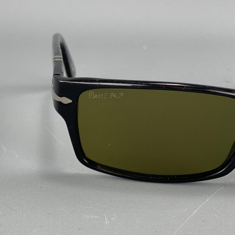 PERSOL sunglasses come in black acetate with silver tone accents and green rectangular lenses. Made in Italy.  Good Pre-Owned Condition. Marked: 2747-S 95/24 57 16 140 3F  Measurements:  Length:14 cm. Height: 3.75 cm.