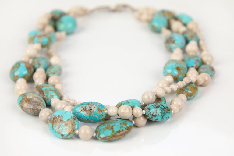 A three-strand necklace of blue Peruvian opals, river stone jasper, and tiny freshwater pearls. Each strand stacks on the next, strand on strand. The necklace comes together with our signature White Orchid Studio vanilla bean clasp, created in 14kt