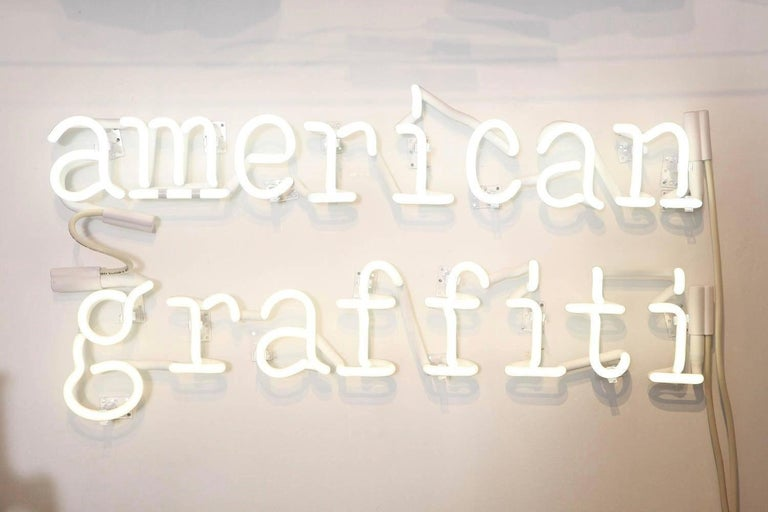 Contemporary artist Peter Buchman's American Graffiti Neon is in white for a reason. It's clean, clear, not cluttered, not everywhere and not obnoxious. The phrase is about his continued introspection of words and writing as well as our American