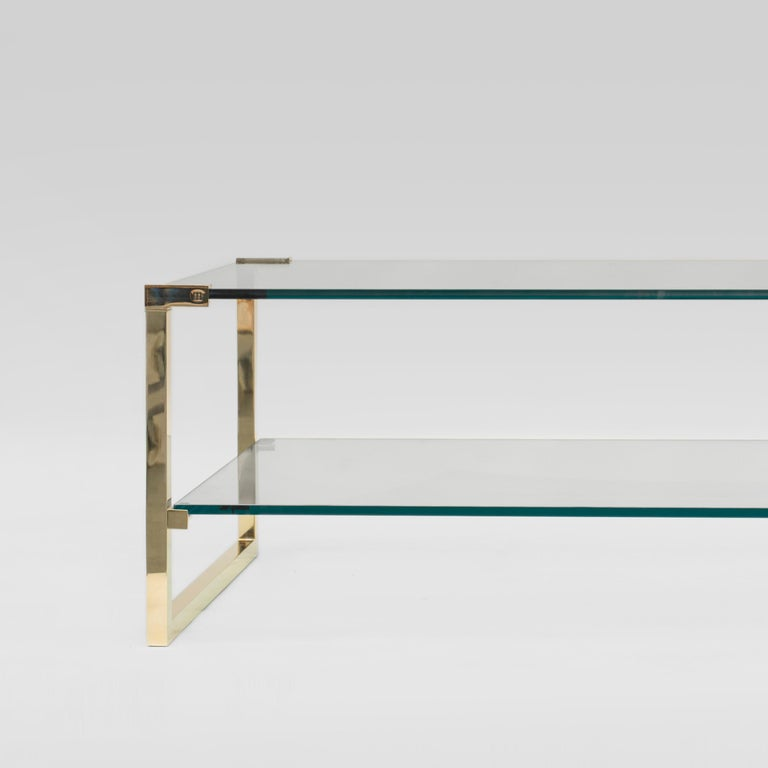 Contemporary coffee table designed by Peter Ghyczy. Manufactured by Ghyczy (Netherlands)  Frame brass gloss Cast part brass gloss Clear glass  Dimensions: L 140 x W 70 x H 50 Dimensions cast part L 9 x W 3x H 3  The twin frames are