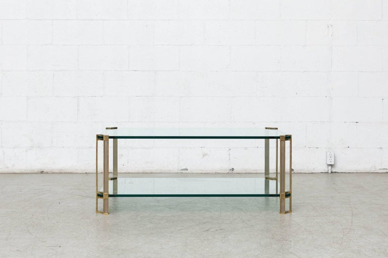 Double tiered brass and floating glass coffee table. Peter Ghyczy studied architecture with an industrial design background at the Polytechnic University Aachen, and is recognized for his famous 1968 garden egg chair. He is also attributed to
