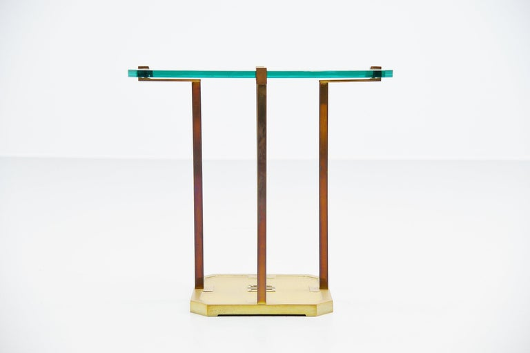 Sculptural brass side table designed and manufactured by Peter Ghyczy, Holland, 1985. This table has a solid brass sculptural frame with a square hardend glass top. Very nice shaped side table by Peter Ghyczy. In the base there is a typical monogram