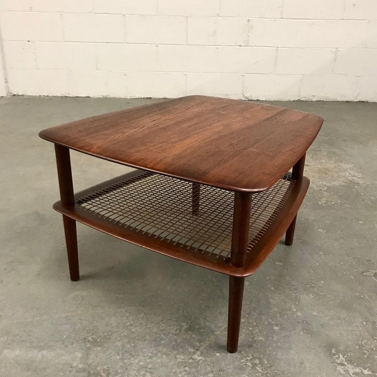 Danish modern, teak side table by Peter Hvidt and Orla Molgaard Nielsen for France & Daverkosen features 2 tiers with caned lower shelf. Measures: The table tapers from 19.5 to 25.5 inches with the lower shelf height at 10 inches.