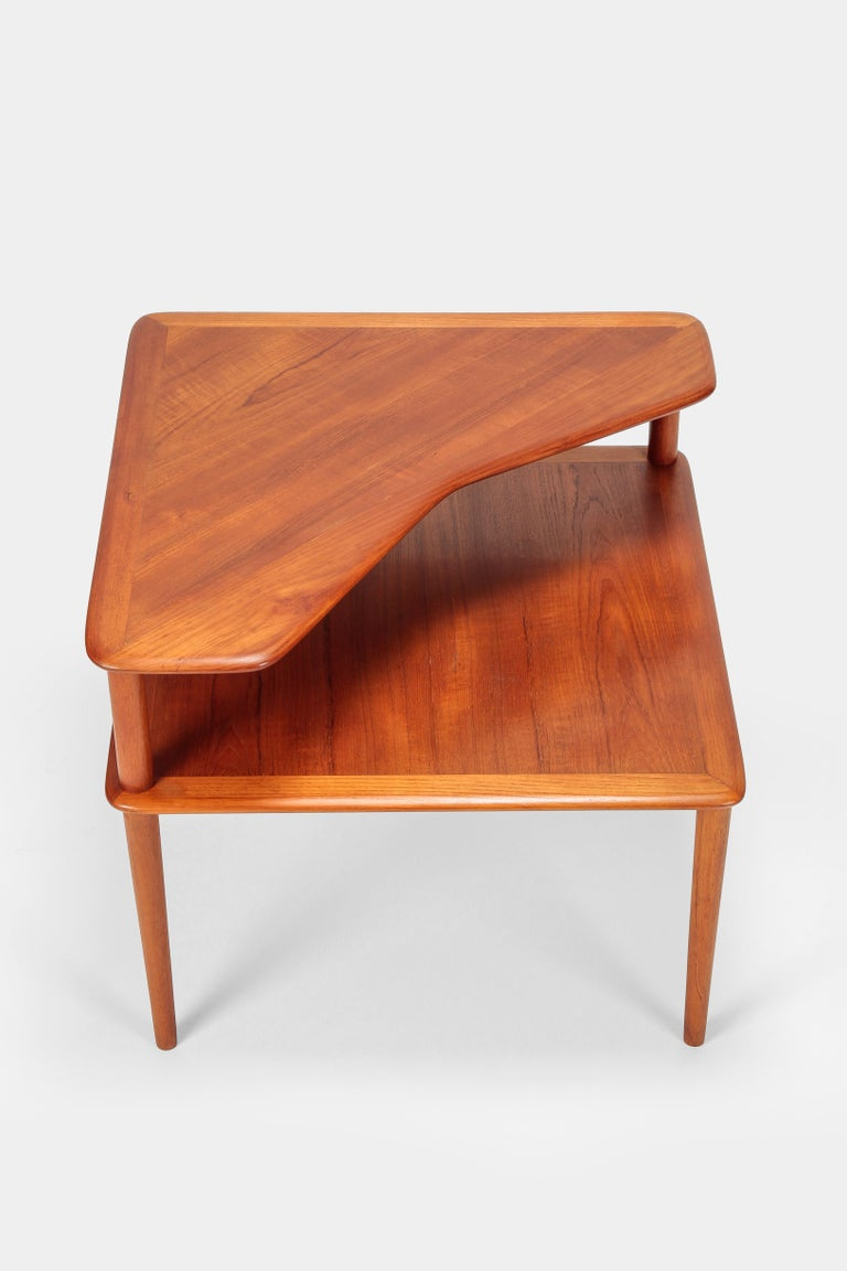 Corner side table with two shelves made in Denmark by France and Son. Designed by Peter Hvidt & Orla Mølgaard Nielsen in solid teak. Natural, organic shape, light colored and beautifully textured. High production quality and quintessential Danish
