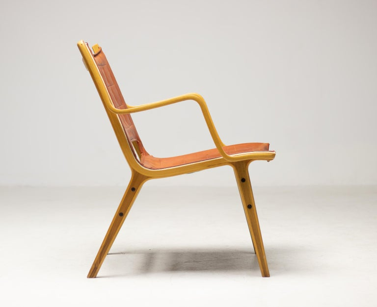 Armchair designed by Peter Hvidt and Orla Mølgaard–Nielsen and produced by Fritz Hansen, Denmark.  The chair is press shaped in laminated beechwood, the seat is upholstered with all original cognac leather.  The legs feature a teak core. An