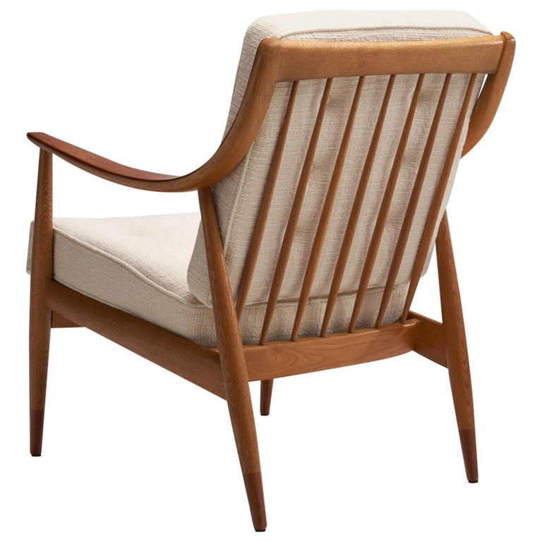 """This is a beautiful Peter Hvidt & Orla Mølgaard-Nielsen designed model """"FD 144"""" easy chair, made in Denmark in 1953. It was produced by France & Daverkosen, Denmark.  This solid oak FD-144 easy chair by the designer duo, has distinctive, wide and"""