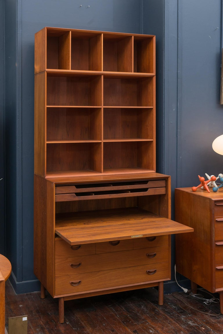 Tall Danish teak secretary bookcase designed by Peter Hvidt & Orla Mølgaard, Denmark. The locking secretary section has two pull out paper trays and five drawers. The upper bookcase has adjustable shelves and is finished off with a file or book