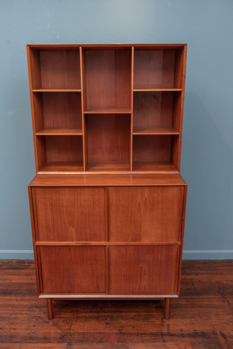Peter Hvidt & Orla Molgaard Nielsen design bookcase cabinet, Denmark. High quality construction in solid teak with dovetail joinery and adjustable shelves throughout. Unusual lower sliding doors that glide smoothly without effort concealing two