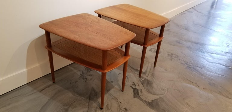 A pair of teak Danish Modern end tables designed by Peter Hvidt for France and Son. Crafted in solid teak with a woven cane magazine shelf under tabletop. Conical legs and woven wicker detail. Tables are in good, original vintage condition with