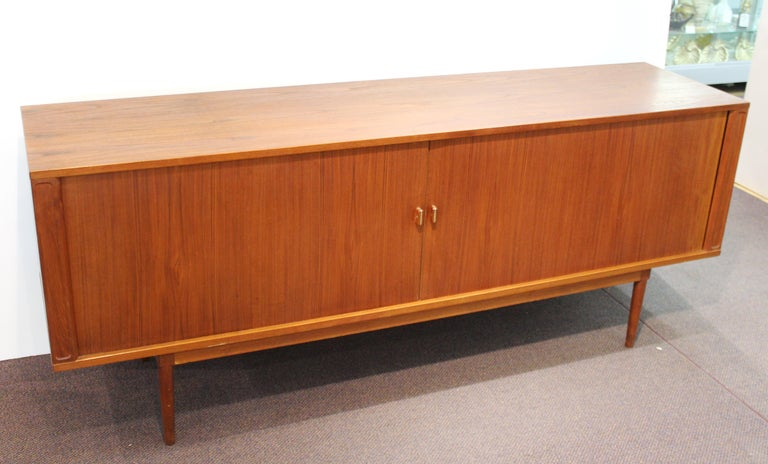 Danish modern credenza designed by Peter Løvig Nielsen in the 1960s. The piece has two tambour doors that slide open to reveal two compartments with storage shelving and one central compartment with flat tray drawers. The pulls have metal accents.