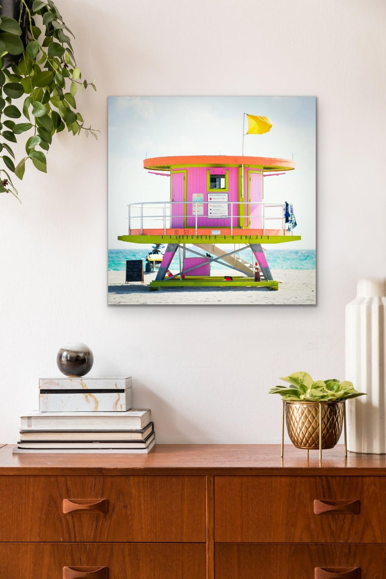 This contemporary coastal photograph by Peter Mendelson features a bright pink, orange, and lime green lifeguard stand on Miami Beach in Florida. The modern-looking, circular structure, sits on the sand with a bright blue and lightly cloudy sky