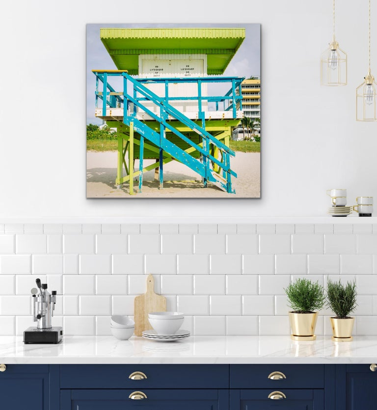 This contemporary coastal photograph by Peter Mendelson depicts a bright blue, lime green and white lifeguard stand  in Miami Beach, Florida. The stand, which has white shut doors that say