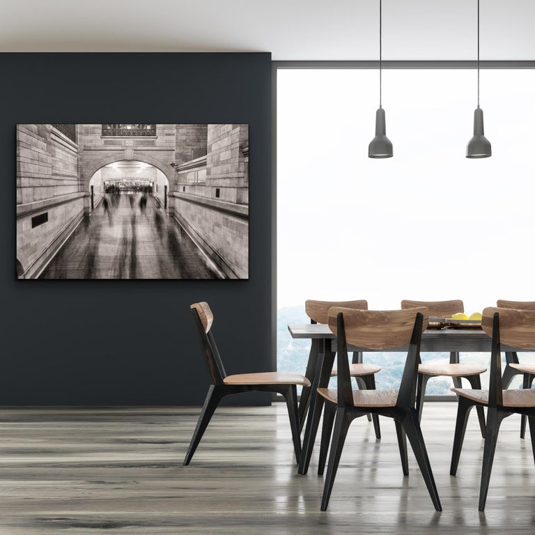 This black and white, urban architectural photograph by Peter Mendelson was taken in Grand Central Station in Manhattan. The artist has captured the still, stately nature of this landmark building, while the moving commuters, tourists, and city