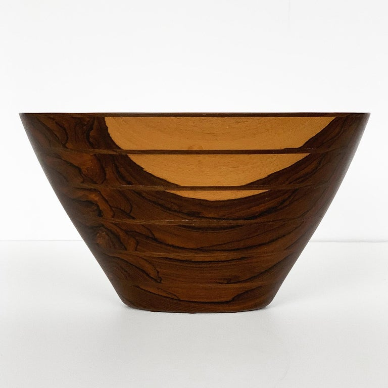 Handcrafted wooden bowl by Peter M Petrochko. Carved laminated padauk and ziricote woods. Signed and dated July 1987. Oval shaped bowl with dramatic grain patterning. Base measures: 4.5