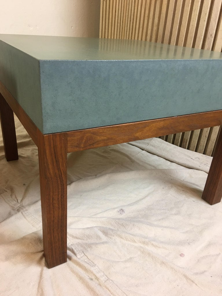 Peter Sandback pair low slung square tables made of a composite cement like material with solid walnut bases. Perfect to use as 2 end tables or together as a coffee table. Top surface is a greenish color.