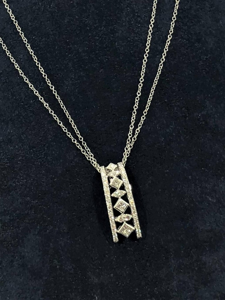 Peter Storm 18 karat white gold and diamond pendant necklace. This pendant is created in 18 karat white gold weighing 5.1 grams/ 3.2 dwt. Set in this design are 4 Princess cut diamonds equaling .40 carats total weight, and 40 full cut round diamonds