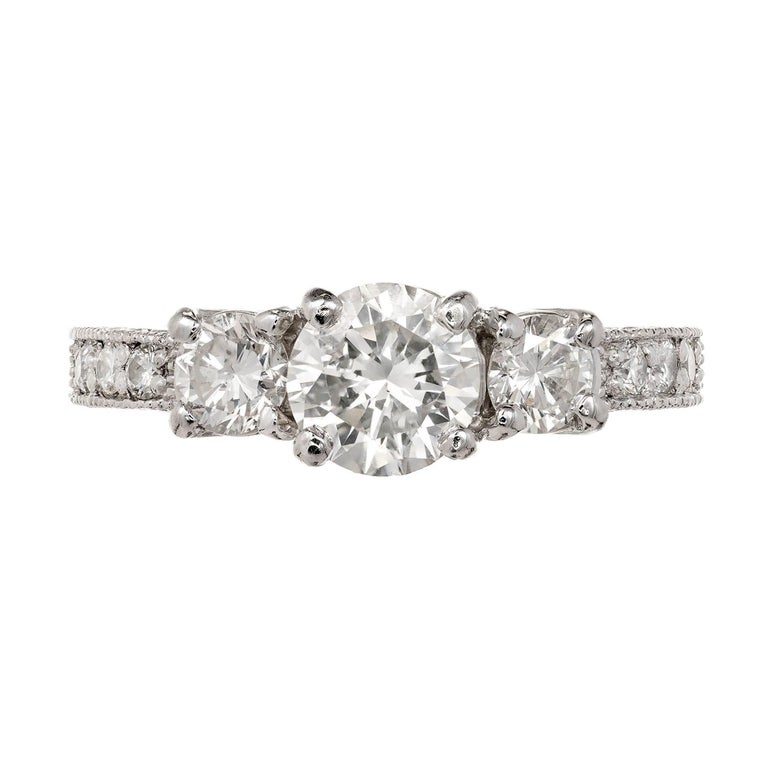 Peter Suchy vintage style custom made three-stone diamond platinum engagement ring.  GIA certified 1.00 carat sparkly center diamond flanked by two equally bright side diamonds in a curved prong top. The shoulders are mil-grained and set with full