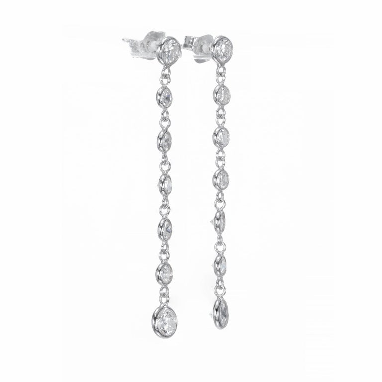Hand crafted diamond bezel dangle drop earrings. 14 full cut diamonds in 14k white gold.    14 full cut diamonds, G to H color, VS1 to SI1 clarity, approx. total weight 1.50cts 14k White Gold Stamped: 14k 80 grams Top to bottom: 1.56 inches or
