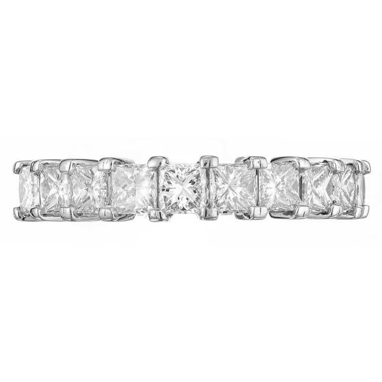 Princess cut diamond wedding band. 11 diamonds in a common prong set platinum setting that goes half way across the finger. Set low to the finger. Crafted by the Peter Suchy Workshop.  11 Princess cut diamonds, approx. total weight 1.75cts, F, VS1