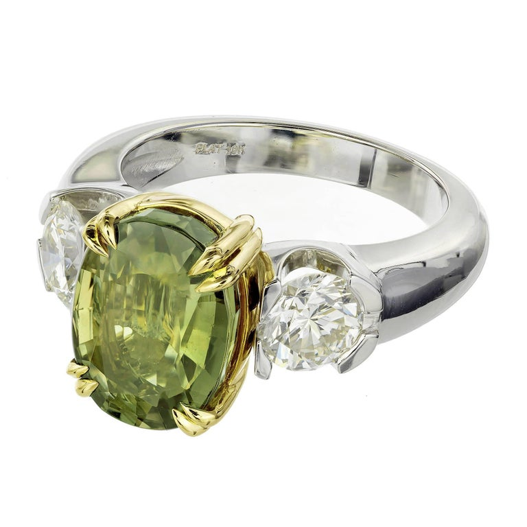GIA certified natural oval Alexandrite and diamond three-stone engagement ring. moderate color change. The Alexandrite is from an estate. The platinum and 18k yellow gold setting is handmade in the Peter Suchy workshop. The diamonds have fantastic