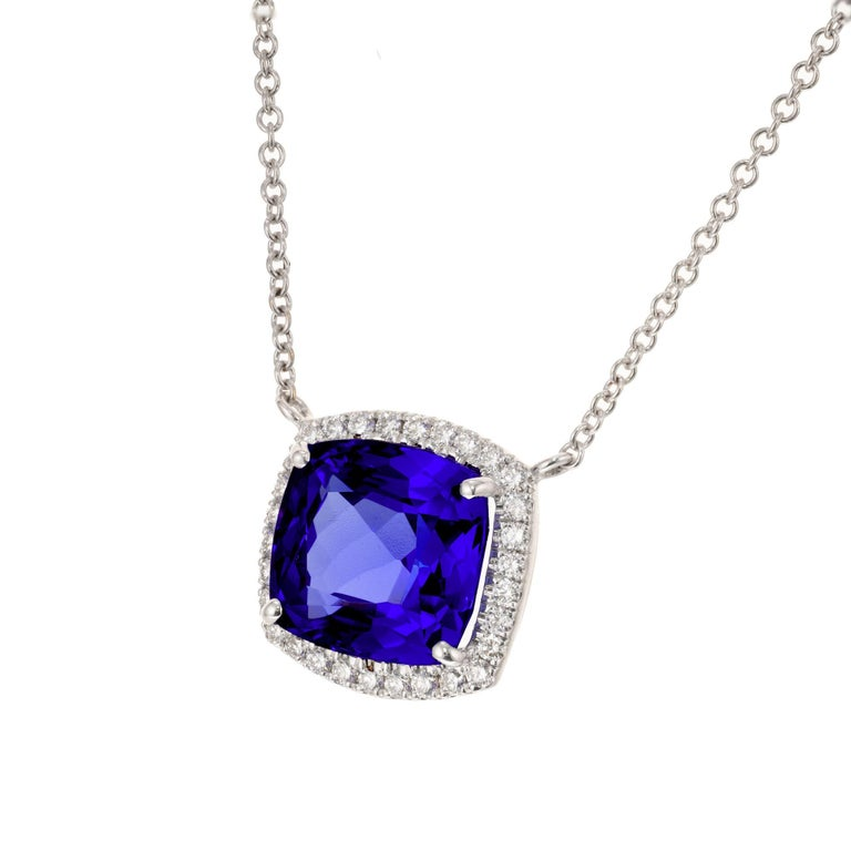 Tanzanite and diamond pendant necklace. 6.18ct cushion cut center tanzanite set in 18k white gold with a halo of 30 round brilliant cut diamonds. 18-inch 18k white gold chain.  1 cushion square cut blue tanzanite, approx. 6.18cts 30 round brilliant