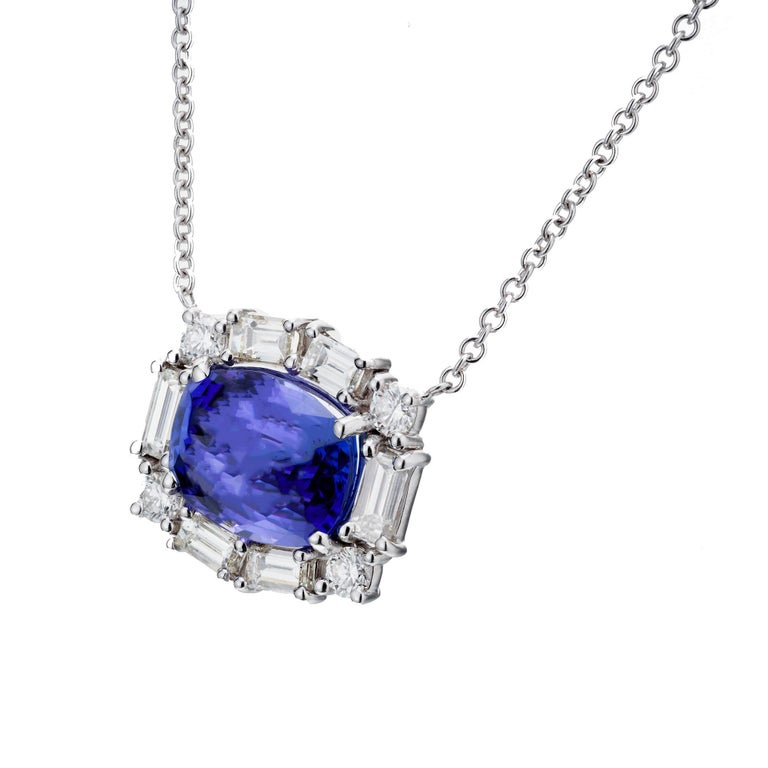 Tanzanite diamond halo pendant necklace. Cushion tanzanite center stone with a baguette and round diamond halo set 18k white gold. Chain length 19 inches. Crafted in the Peter Suchy Workshop.    1 cushion blue tanzanite, approx. 6.56cts 6 straight