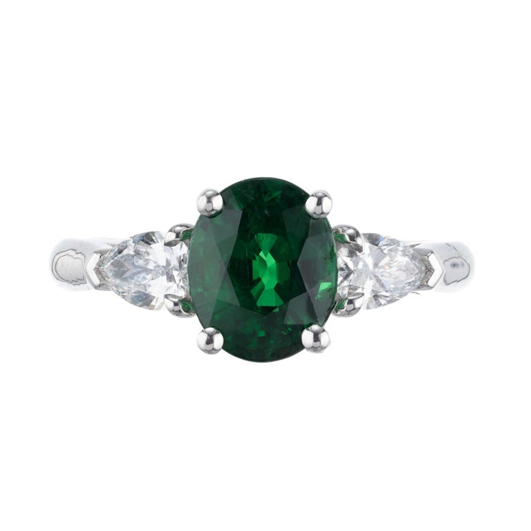 Green Tsavorite Garnet and diamond three-stone engagement ring. 2.30ct oval center stone with two pear shaped side diamonds in a platinum setting. Created in the Peter Suchy Workshop. GIA Certified.   1 oval bright green Garnet, approx. total weight