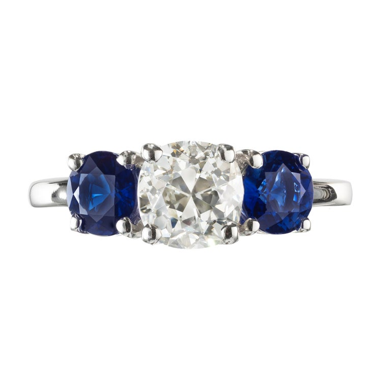 1.50 carat old mine brilliant cut diamond and sapphire three-stone engagement ring. With raised crown and small table. GIA center stone set in a platinum setting with two round accent sapphires. Designed and crafted in the Peter Suchy Workshop.   1