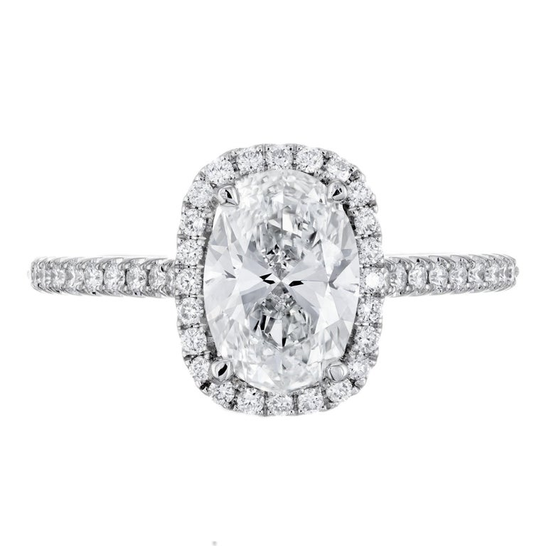 Oval diamond engagement ring. GIA Certified oval center stone with a halo of round diamonds in a platinum setting. Created in the Peter Suchy Workshop.   1 oval brilliant cut diamond H, VS, approx. 1.51cts GIA Certificate # 2191689944 46 round