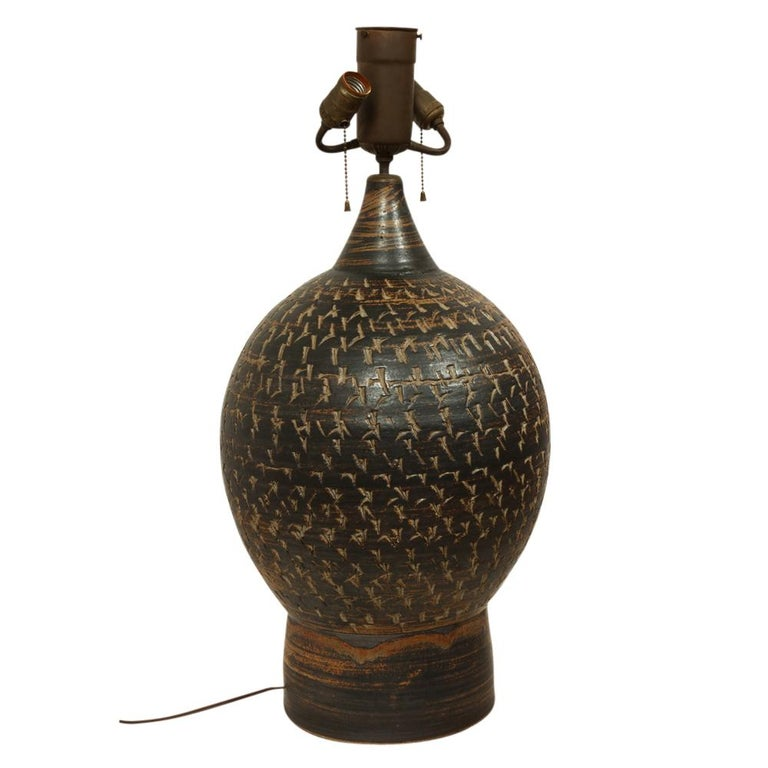 Peter Voulkos stoneware lamp earth tones ceramic pottery incised signed USA, 1950s. Large hand thrown pottery lamp decorated with an abstract pattern of incised lines. Heavy, weighing at least 40 lbs. Signed Voulkos on the underside. The ceramic
