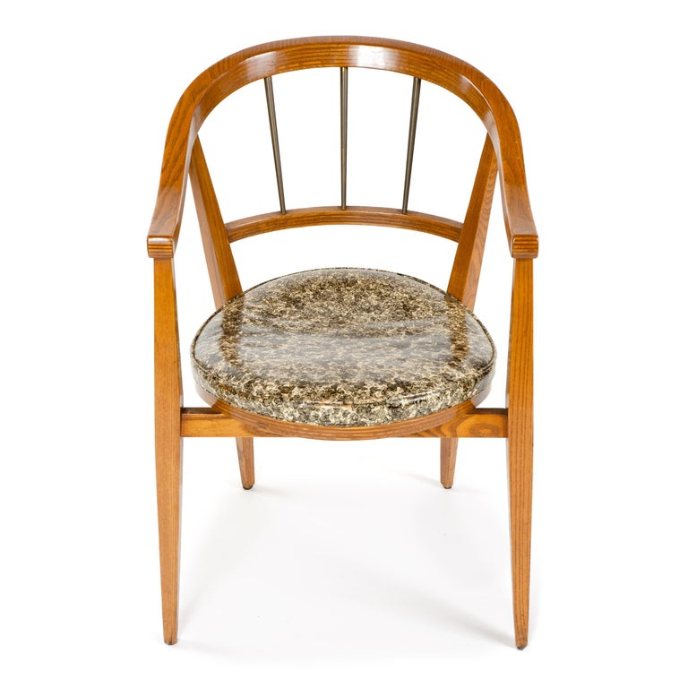 A petite chair in oak with a curved backrest and arms, having tapered legs, brass spindles and a floating upholstered seat.