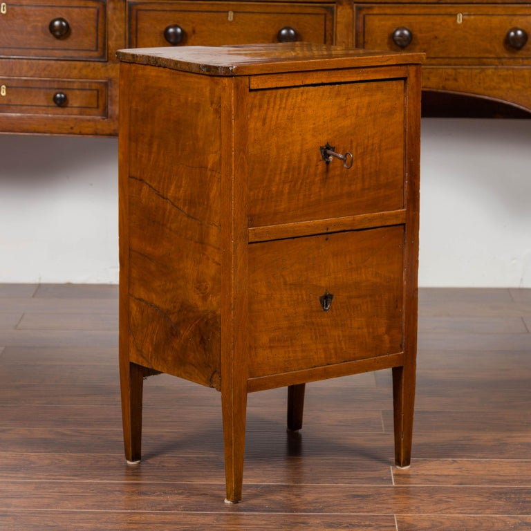 A petite Austrian Biedermeier period walnut commode from the mid-19th century, with two drawers and shield-shaped escutcheons. Born in Austria during the second quarter of the 19th century, this Biedermeier walnut commode features a rectangular top
