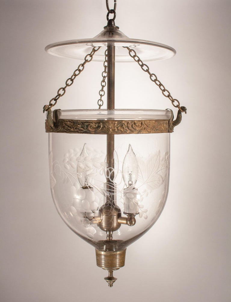 A charming 19th century English bell jar lantern with etched grape and leaf motif. This circa 1860 petite pendant features a period embossed brass band and finial candleholder base. The quality of the hand blown glass is excellent, with desirable