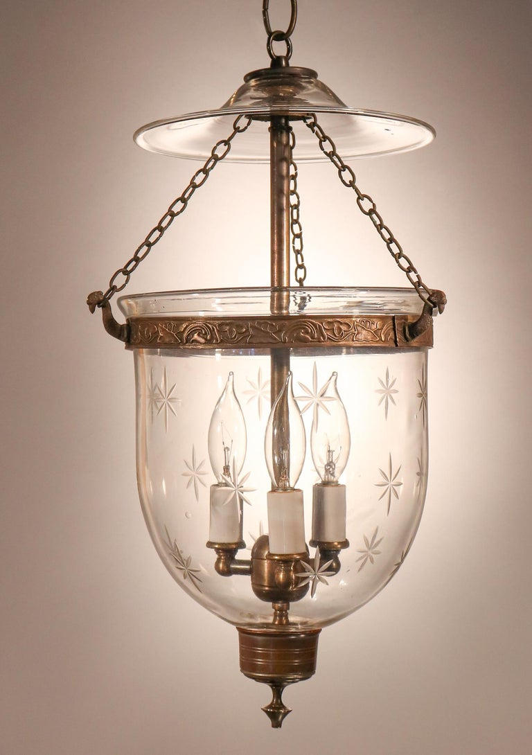 An antique English bell jar lantern with lovely form complemented by a finely etched star motif. This petite, circa 1890 pendant features very good quality hand blown glass complemented by an embossed brass band and simple candleholder base with
